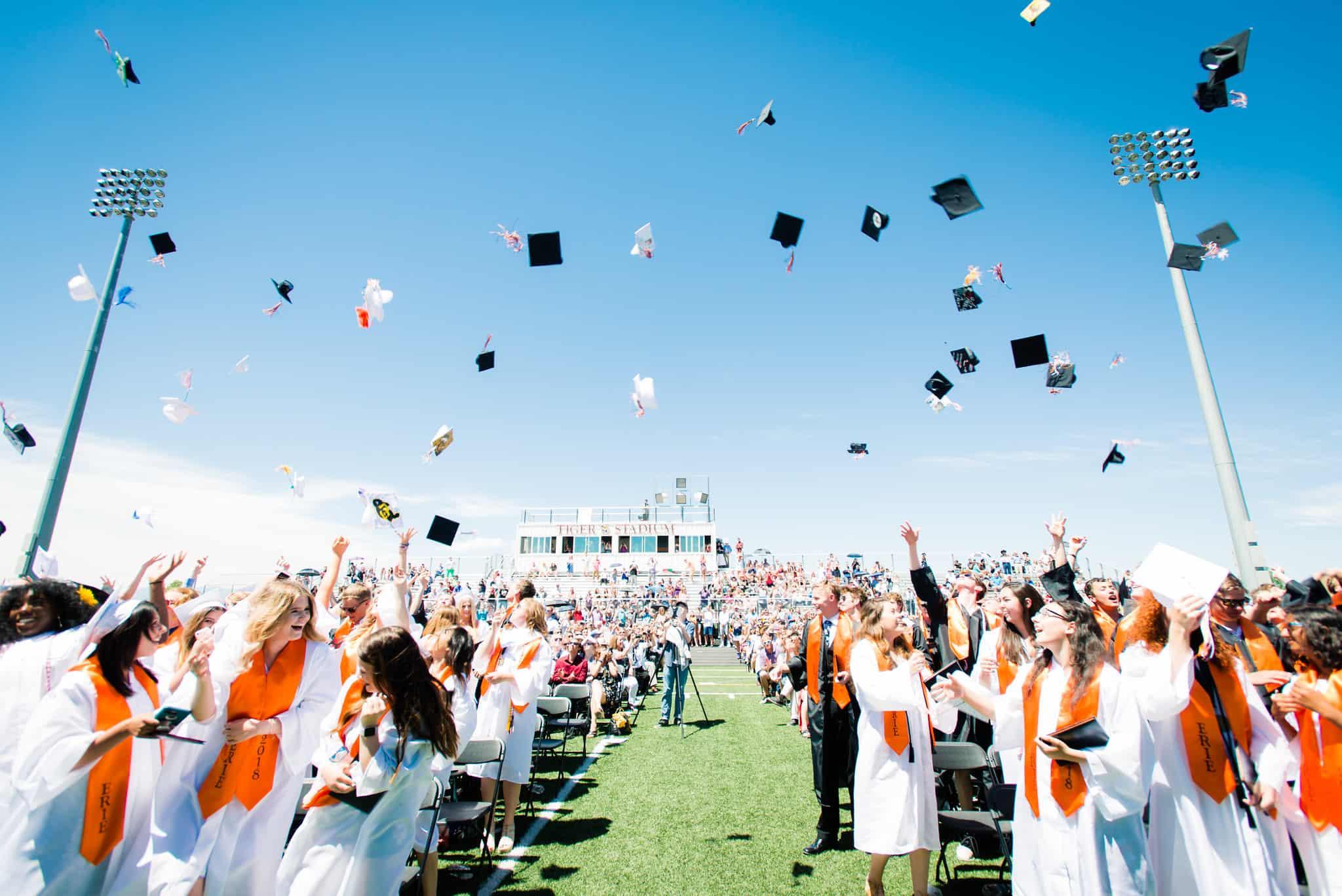 students tossing caps at graduation